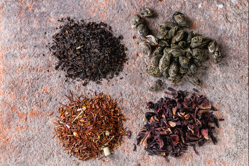Variety of black, green, rooibos and herbal dry tea leaves on old terracotta board as background. Top view, close up